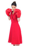 Elegant brunette in red dress wearing boxing gloves Royalty Free Stock Photography