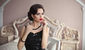 Elegant brunette with retro hairstyle posing in luxurious interi Royalty Free Stock Photo