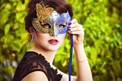 Elegant brunette with venetian mask Stock Photos