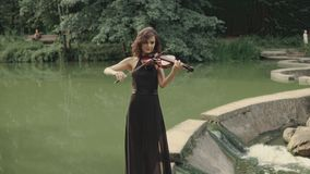 Elegant brunette violinist in forest plays on bridge outdoors. Elegant brunette violinist in forest. Young beautiful girl in black dress plays violin staying on stock video