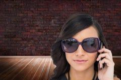 Elegant brunette wearing sunglasses on the phone. Composite image of elegant brunette wearing sunglasses on the phone in room with brick lined wall royalty free stock photo