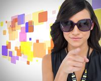 Elegant brunette wearing sunglasses pointing at camera Stock Image