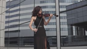 Elegant woman in black dress playing violin near glass building. Art concept stock video footage