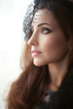 Elegant brunette woman in hat with veil looking out window, prof Royalty Free Stock Photo