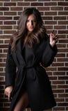 Elegant brunette girl with long curly hair wearing coat, posing near brick wall royalty free stock photos