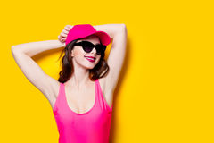 Elegant brunette woman in pink swimsuit and fashion cap. Sexy la. Dy in pink beachwear, sunglasses enjoying sun on yellow summer background Royalty Free Stock Image