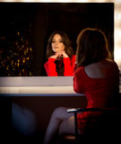 Elegant brunette woman in red dress sitting at mirror Stock Photos