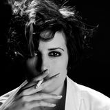 Elegant brunette woman smoking a cigarette on black background Stock Photos