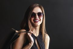 Black Friday Shopping. Elegant brunette woman wears sunglasses and black dress holding black shopping bags, black friday concept Royalty Free Stock Images
