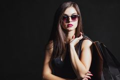Black Friday Shopping. Elegant brunette woman wears sunglasses and black dress holding black shopping bags, black friday concept Stock Photo