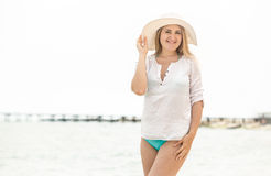 Elegant brunette woman in white hat posing against seashore Stock Photography