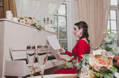 Elegant brunette 30-35 year old woman pianist in evening red dress sits at the retro piano, looking on musical notes in royalty free stock photo