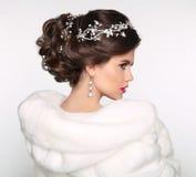 Elegant brunettkvinna i det vita pälslaget den härliga gulliga frisyren låser model ståendeprofilbröllop _ Royaltyfri Foto