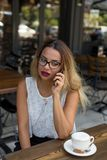 Elegant business female in an outdoor cafe speaking over mobile phone royalty free stock photography