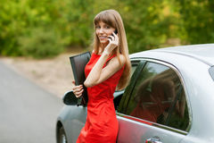 Elegant business lady in a red dress standing in front of her ca. R. She is holding a black folder with documents and talking on the phone Stock Image