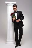 Elegant business man holding a bouquet of red roses. Full body picture of a elegant business man holding a bouquet of red roses in his hands while leaning on a Stock Photography