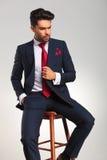 Elegant business man holding his coat while sitting Royalty Free Stock Photo