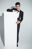 Elegant business man leaning on a white board Royalty Free Stock Photo