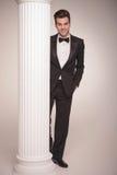 Elegant business man posing behind a white column Royalty Free Stock Images