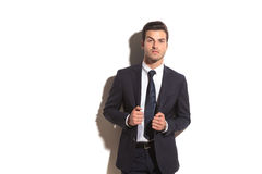 Elegant business man pulls his coat's collar Stock Images