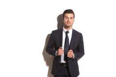 Elegant business man pulls his coat's collar Stock Images