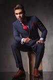 Elegant business man sitting on a wood box while thinking. Stock Photo