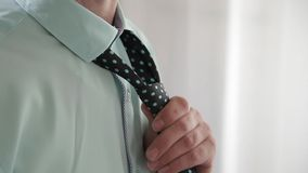 Elegant business man in white shirt correcting his tie and buttoning his suit jacket. close up. stock footage