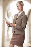 Elegant business woman with a clipboard. Trendy businesswoman with a clipboard, looks up Royalty Free Stock Image