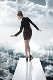Elegant business woman in the financial crisis. Formal business woman wearing dark elegant suit, turned on back,  keeping her balance on the unstable trampoline Stock Photo