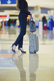 Elegant business woman with hand luggage in international airport terminal Royalty Free Stock Photo