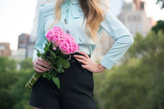 Elegant business woman holding roses bouquet against city background Stock Photos