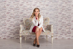 Elegant business woman sits on sofa Stock Images