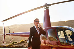 Elegant business woman. Talking by phone near the helicopter. Business, success and luxury concept Royalty Free Stock Photography