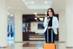 Elegant Business Woman with Travel Trolley Luggage in Hotel Lobby. Female executive with suitcase in work related business trip Royalty Free Stock Photos