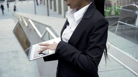 Elegant business woman typing on laptop outside office building, online service. Stock photo stock photography