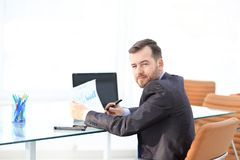 Elegant businessman analyzing data in office. Elegant businessman analyzing data in white office Stock Photo