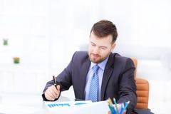 Elegant businessman analyzing data in white office. Elegant business man analyzing data in office Stock Photo
