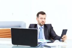 Elegant businessman analyzing data in office. Elegant businessman analyzing data in white office Stock Photography