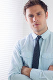 Elegant businessman with arms crossed in office Royalty Free Stock Image