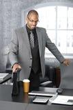 Elegant businessman arriving to office. Elegant afro businessman arriving to office with coffee and briefcase, smiling stock photography