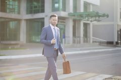 Elegant businessman in blue suit walking out of bank. Elegant businessman in blue suit walking down the street royalty free stock images