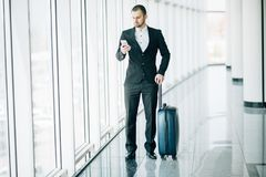 Elegant businessman checking e-mail on mobile phone while walking with suitcase inside airport terminal. Experienced male employer royalty free stock photo