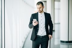 Elegant businessman checking e-mail on mobile phone while walking with suitcase inside airport terminal. Experienced male employer stock photo