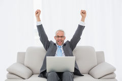 Elegant businessman cheering in front of laptop at home Royalty Free Stock Photography