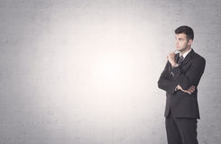 Elegant businessman with clear background. Young sales business person in elegant suit standing in front of clear empty grey wall background while talking on the Royalty Free Stock Images