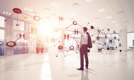 Networking and social communication concept as effective point f. Elegant businessman in 3D office interior and social connection concept. Mixed media Royalty Free Stock Photo