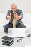 Elegant businessman gesturing thumbs up with laptop at home Stock Photography