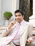 Businessman speaking on cell phone. Elegant businessman having a conversation on a cell phone while sitting at an office building entrance Stock Photo