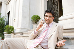Businessman speaking on cell phone. Elegant businessman having a conversation on a cell phone while sitting at an office building entrance Royalty Free Stock Photography