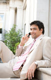 Businessman speaking on cell phone. Elegant businessman having a conversation on a cell phone while sitting at an office building entrance, smiling Royalty Free Stock Images